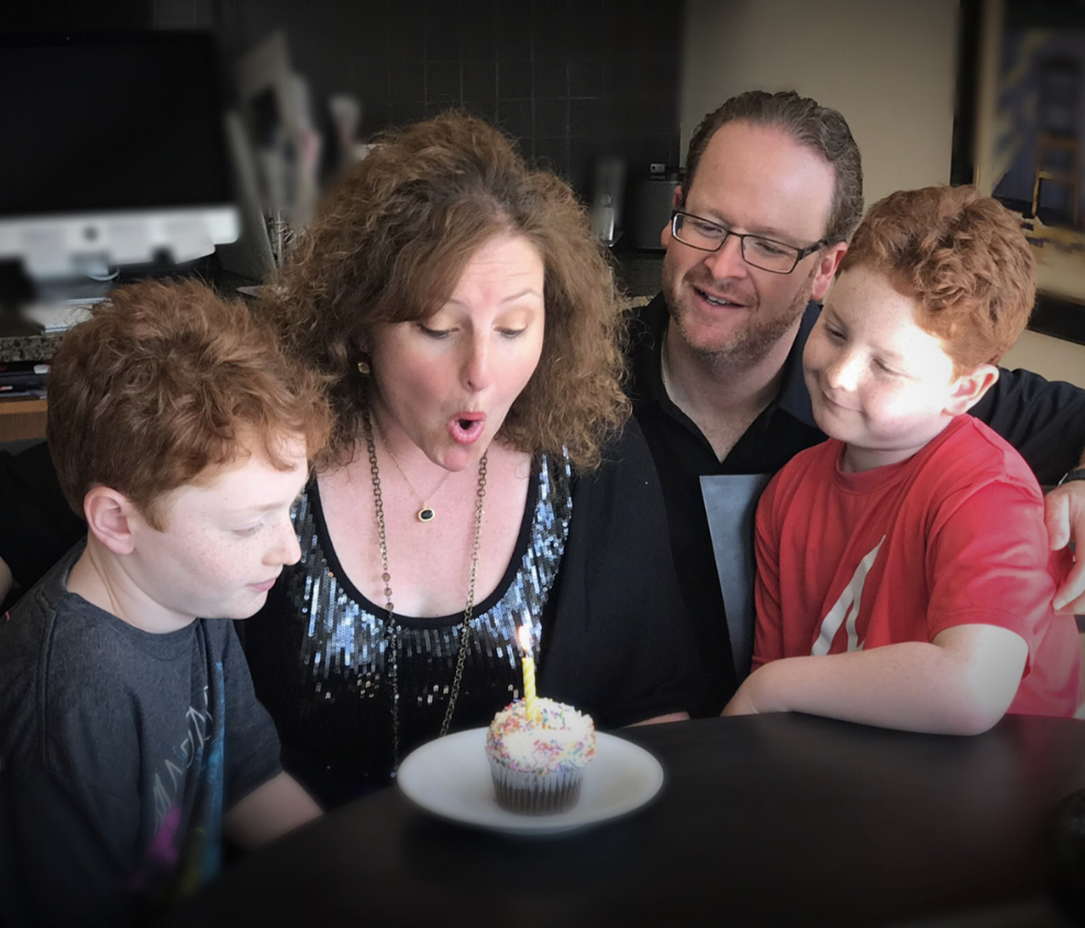 Mom blowing out candle with boys